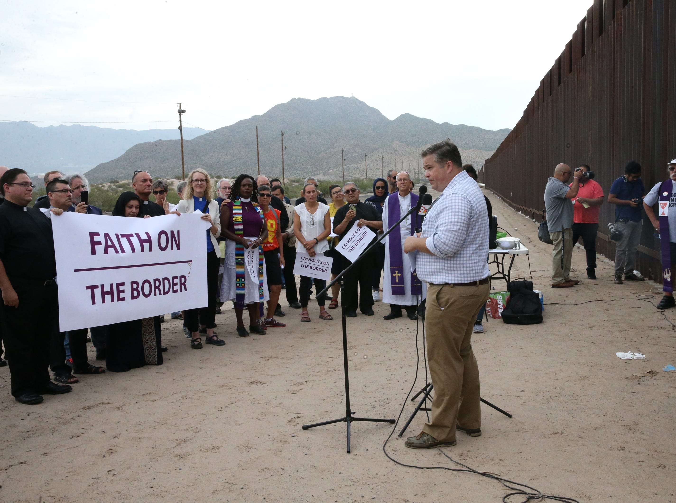 Dylan Corbett, executive director of Hope Border Institute speaks to an interfaith gathering of clergy at the border fence in Sunland Park, N.M. Friday.