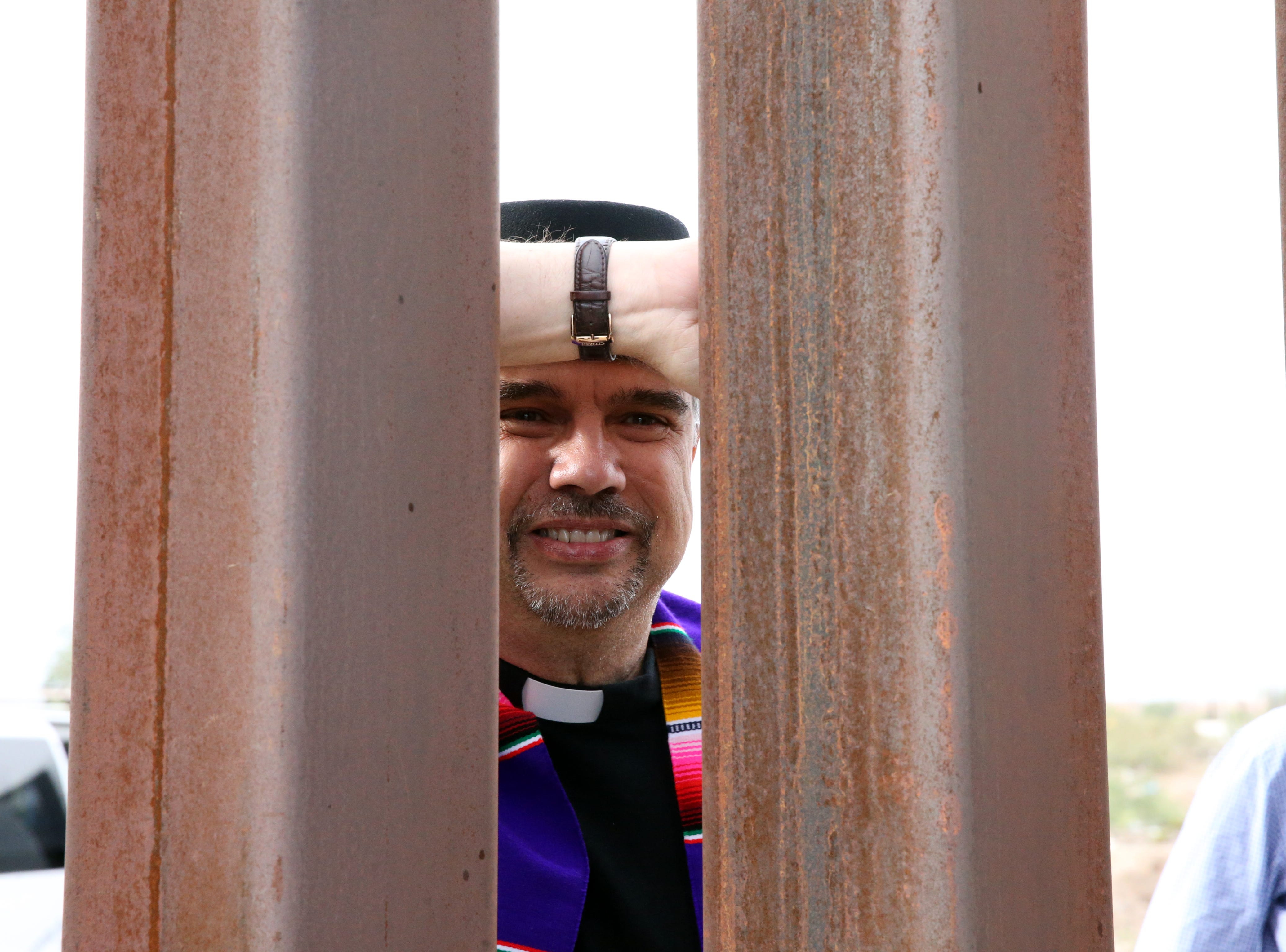 Miguel de la Torre of Iliff School of Theology in Denver, CO. peers through the border fence from the Anapra area of Juarez Friday.