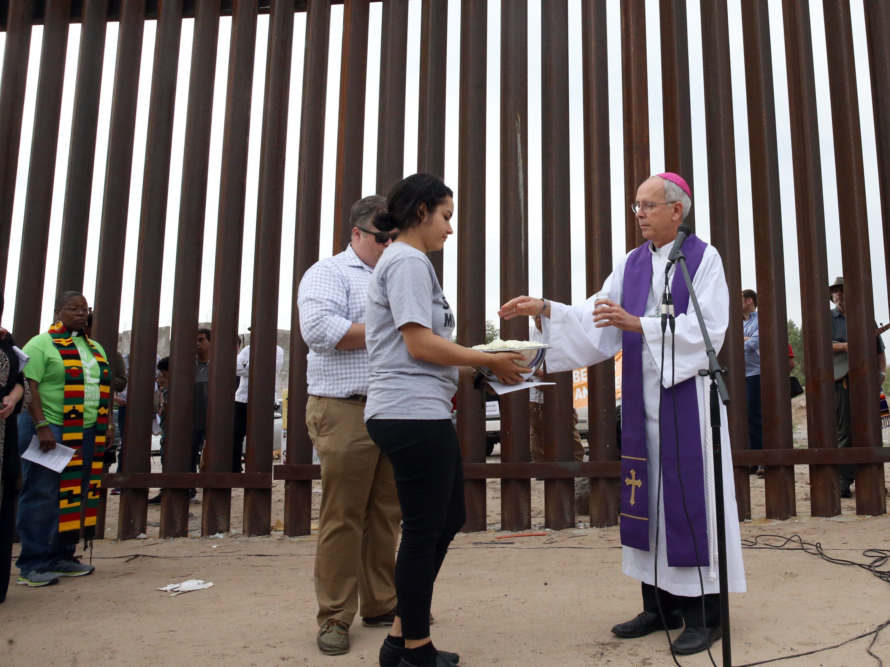El Paso Catholic Bishop Mark Seitz blesses flower petals at the border fence in Sunland Park, N.M. Friday.