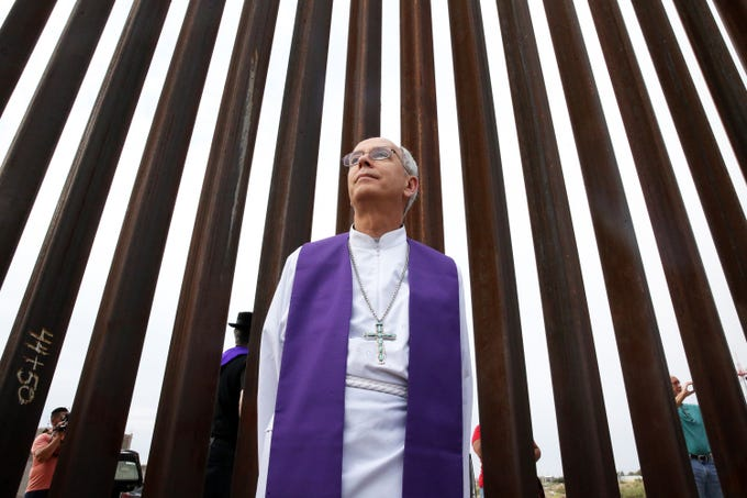 """El Paso Catholic Bishop Mark J. Seitz stands along the border fence at Sunland Park, N.M., during an interfaith gathering of clergy, including many who were visiting from other parts of the country. The clergy members spoke, prayed and visited with people gathered on the Juárez side during a prayer vigil Friday.  Hope Border Institute, a faith-based group focused on defending human rights on both sides of the border, hosted three national delegations to the area. One group, Faith in Public Life, brought 15 Catholic priests, said Camilo Perez Bustillo, director Advocacy and Research for Hope Border Institute. Another was comprised of a network that rose due to immigrant family separations at the border and a third group was called Movimiento de Mujeres y Madres Migrantes, a movement of migrant mothers and women based in New York, Bustillo said. The three groups united under an interfaith framework titled, """"The Cry of the Borders."""" The gathering was to protest the idea of indefinite family detention until individual immigration cases are decided, a plan that was announced Thursday by the Trump administration."""