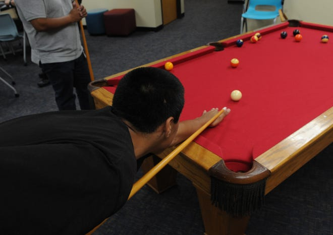 A youth plays pool at the Ventura County Probation Agency's  Keeping Engaged Youth Supported center in Oxnard.