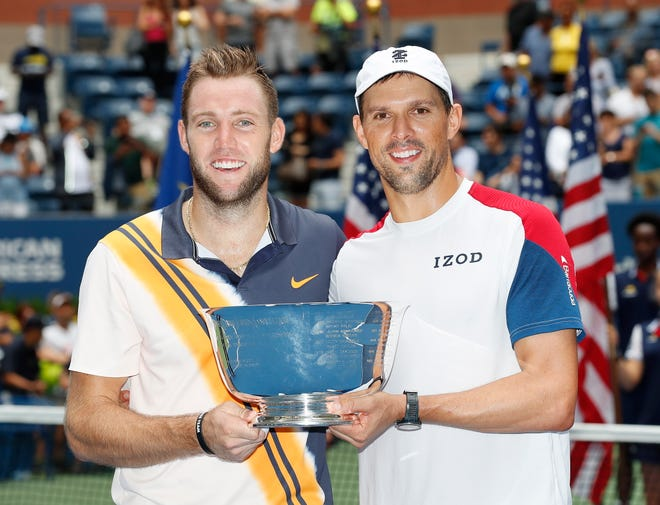 Jack Sock, left, and Mike Bryan pose with the championship trophy after winning the men's doubles final at the U.S. Open in New York on Friday.