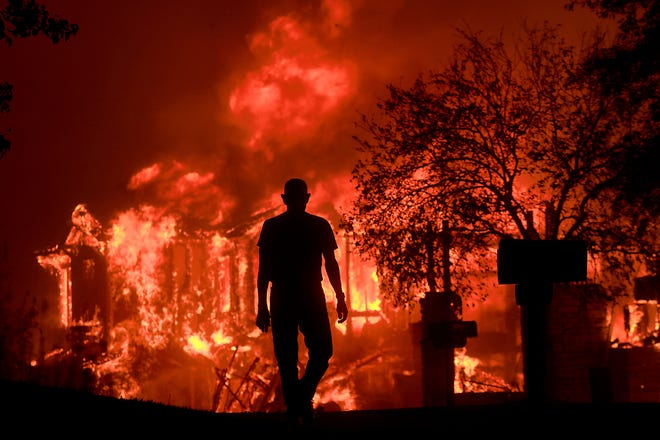 In this Oct. 9, 2017, file photo, structures burn in Fountaingrove. A state investigation has found that staff at two senior care facilities, not shown, abandoned residents during an evacuation as wildfires swept through Northern California.