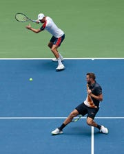 Mike Bryan, left, returns a shot while partner Jack Sock tries to get out of the way during their win over Lukasz Kubot and Marcelo Melo in the men's doubles final of the U.S. Open on Friday in New York.