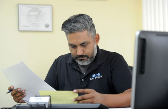 Tony Gurrola Jr., a bail agent with Iron Bail Bonds in Ventura, goes over some paperwork in his office. The state passed a law ending cash bail. Gurrola's job and his co-workers' will likely go away in October 2019.