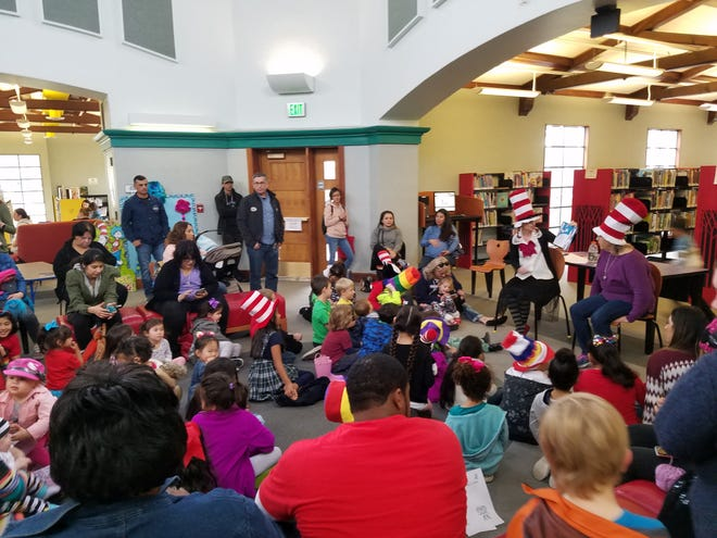 Families gather to celebrate Dr. Seuss' birthday with a Cat in the Hat reading at Tulare County Library