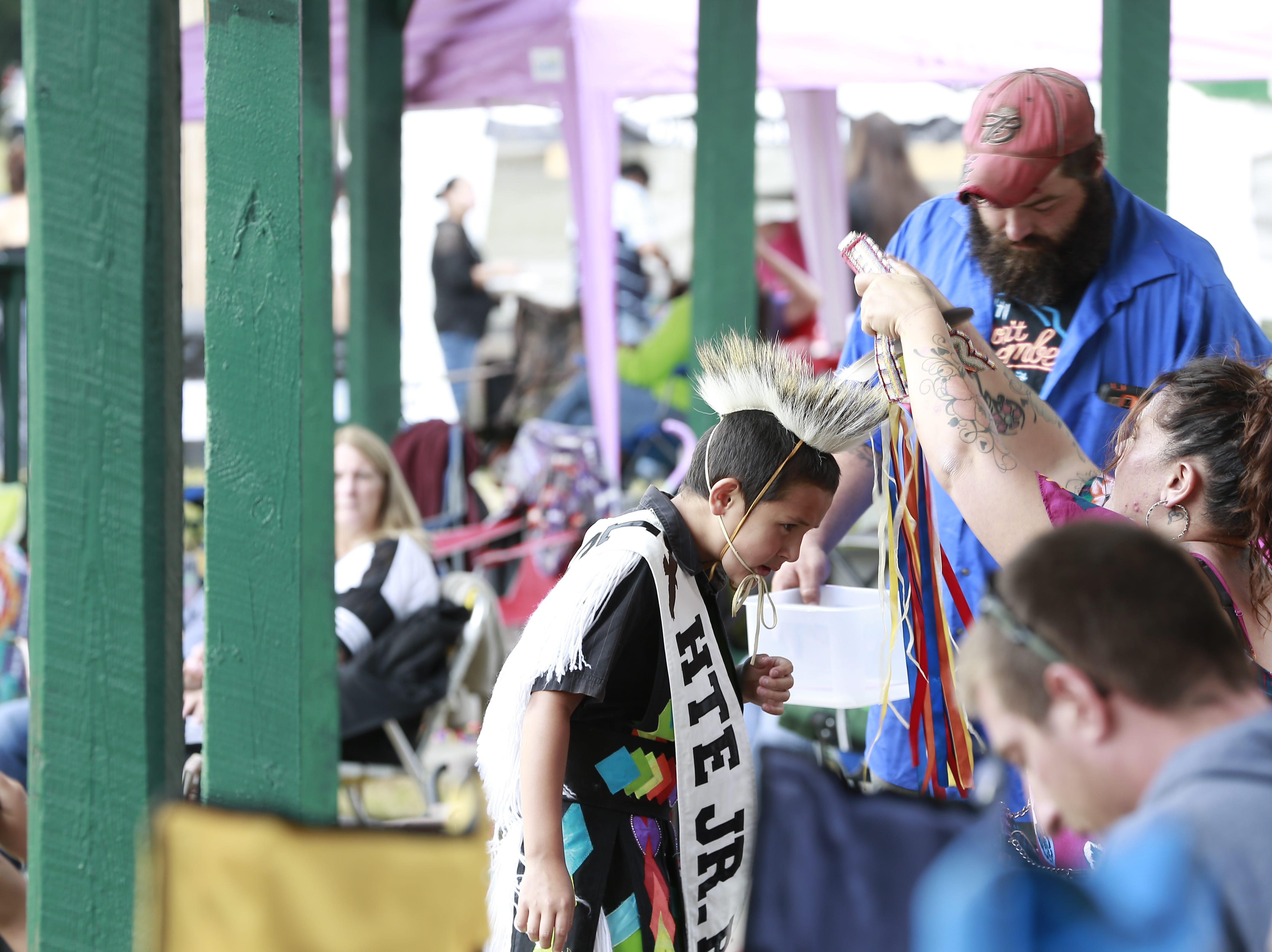 A boy leans over to get his neck wearing put on Friday, July 20, 2018, to celebrate the Honor the Earth Pow-wow event at LCO School in Hayward, Wis.