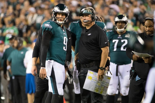 Eagles head coach Doug Pederson, right, speaks with quarterback Nick Foles (9) during a timeout Thursday night at Lincoln Financial Field.