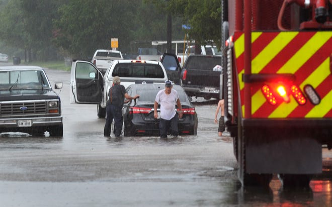 A pickup truck is used to help pull a stranded motorist out of the water after the Fire Department responded to a report of a possible water rescue on Covington Road.