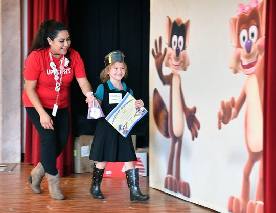 In this file photo, Elizabeth Estrada of Upstart guides a young program graduate onto the stage at the Farris Early Childhood Center.