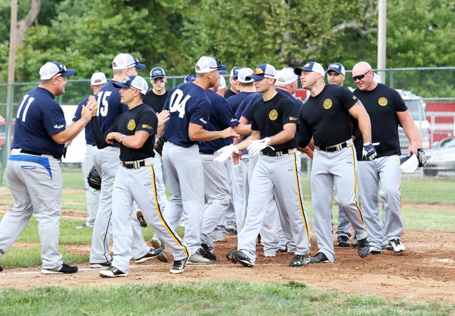 Members of the Muskingum County Sheriff's Office and members of the City of Zanesville fire and police departments greet each other before facing off in a softball game Thursday night at Gant Stadium to help kick off the United Way's 2018 campaign.