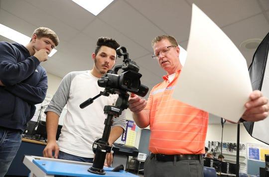 Maysville High School teacher Kurt Dreier asks students Brady Peterson and Justin Neff how to white-balance a video camera during a recent class.