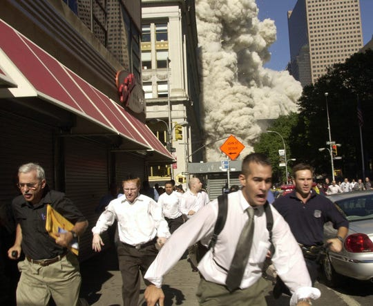 People run from the collapse of one of the twin towers.