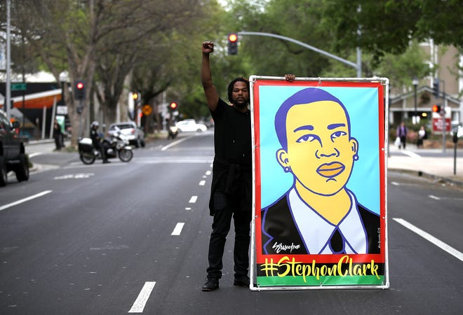 A Black Lives Matter protester holds an illustration of Stephon Clark during a march and demonstration through the streets of Sacramento on April 4, 2018 in Sacramento, California.