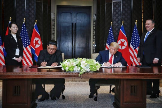 U.S. Secretary of State Mike Pompeo, right, and North Korean leader's sister Kim Yo Jong, left, look on as President Trump and North Korean leader Kim Jong-un sign a document during their historic summit in Singapore, June 12, 2018.