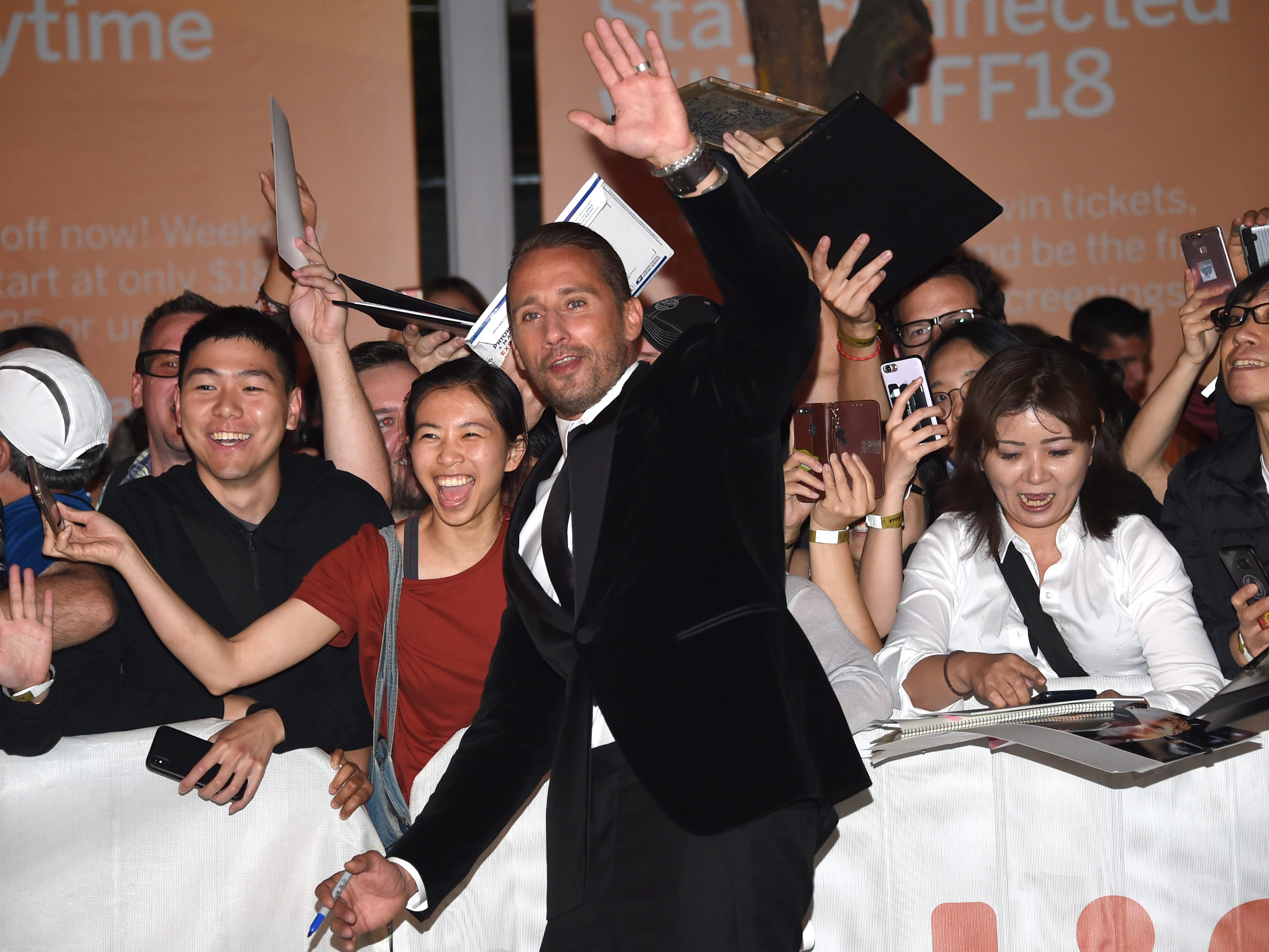 "Matthias Schoenaerts waves to fans before a screening for ""Kursk"" at the Princess of Wales Theatre."