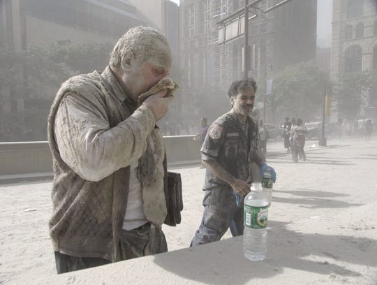 A man coughs as he is coated with ash and debris from the collapse of the World Trade Center.