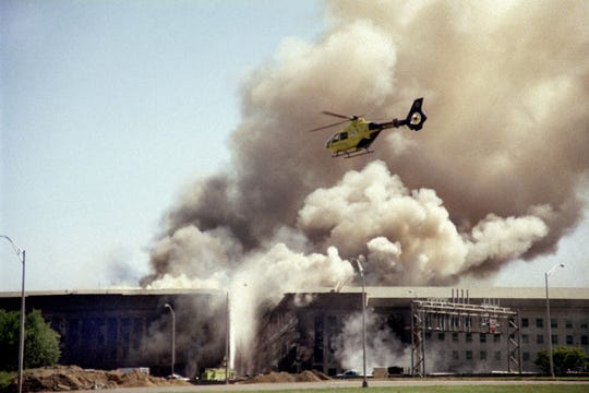 A helicopter flies over the Pentagon in Washington on Sept. 11, 2001 as smoke billows over the building.