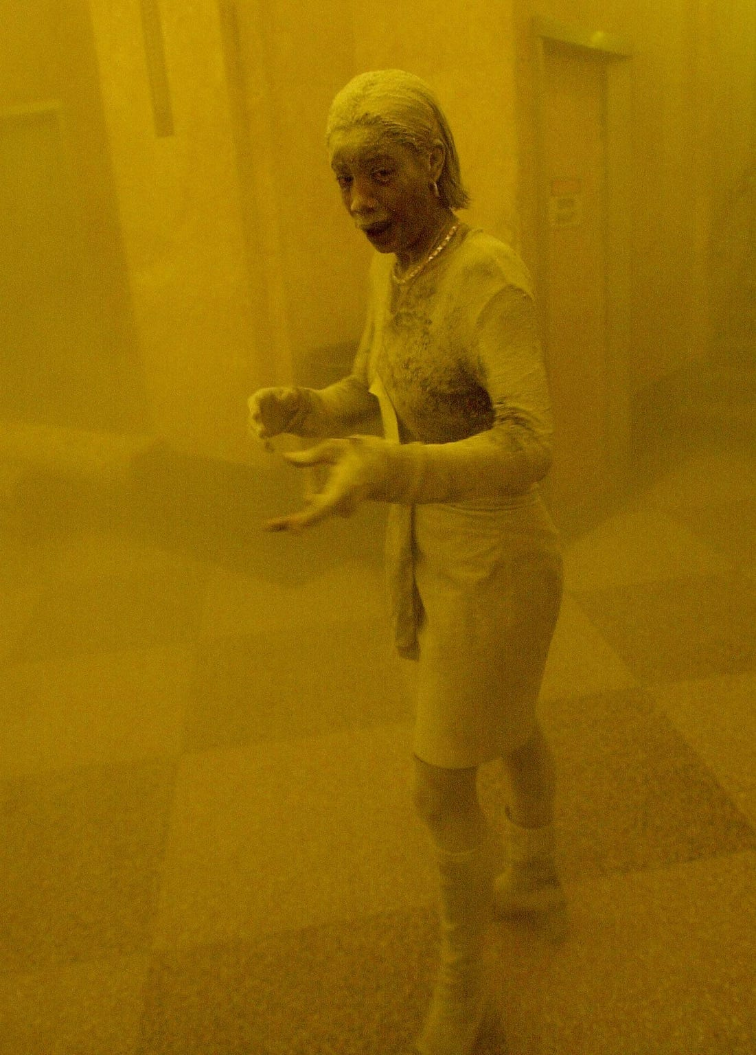 Marcy Borders is covered in dust as she takes refuge in an office building after one of the World Trade Center towers collapsed in New York.