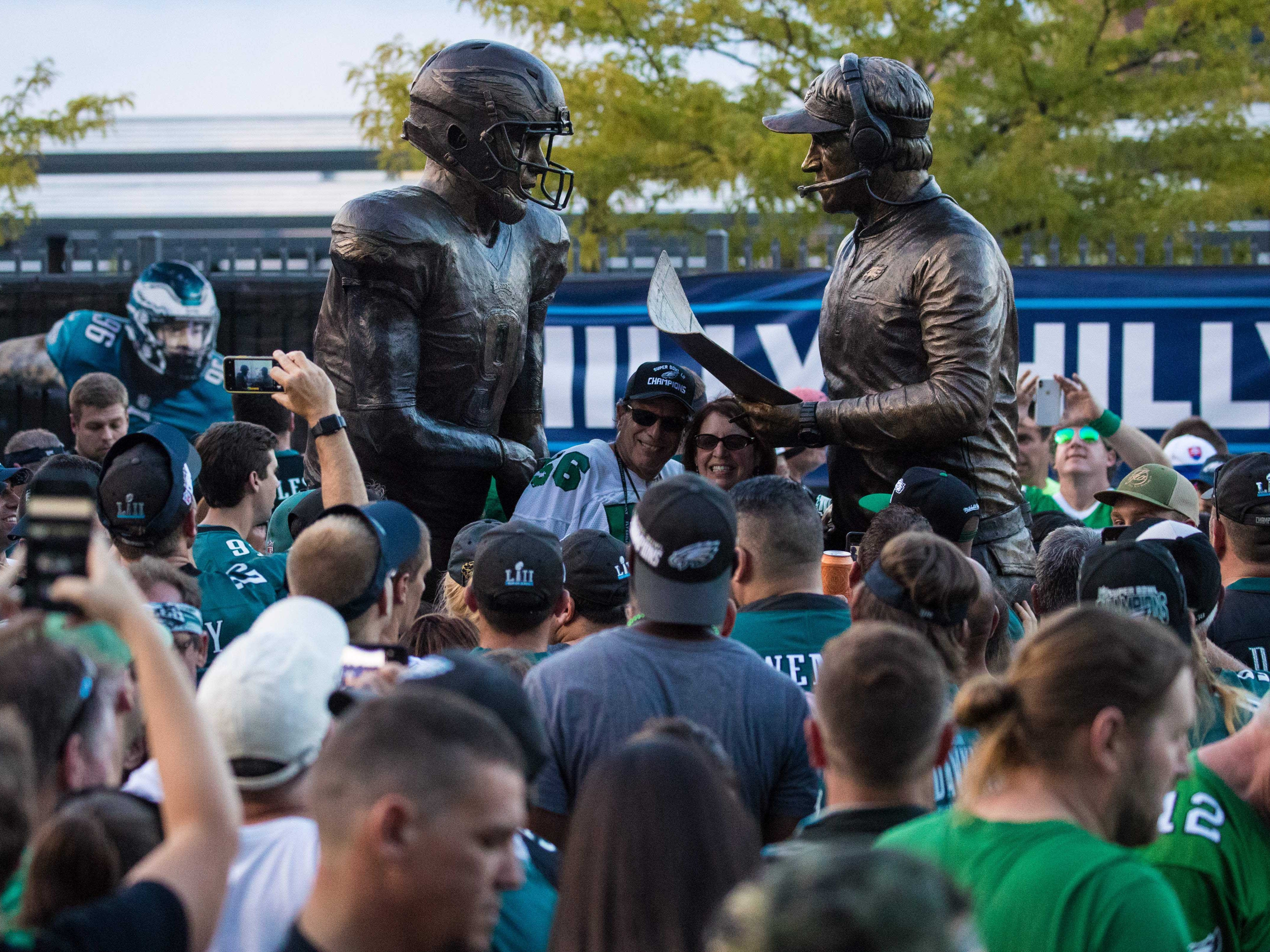 Philadelphia Eagles fans crowd around a new statue depicting head coach Doug Pederson (right) and quarterback Nick Roles (left) during Super Bowl LII.