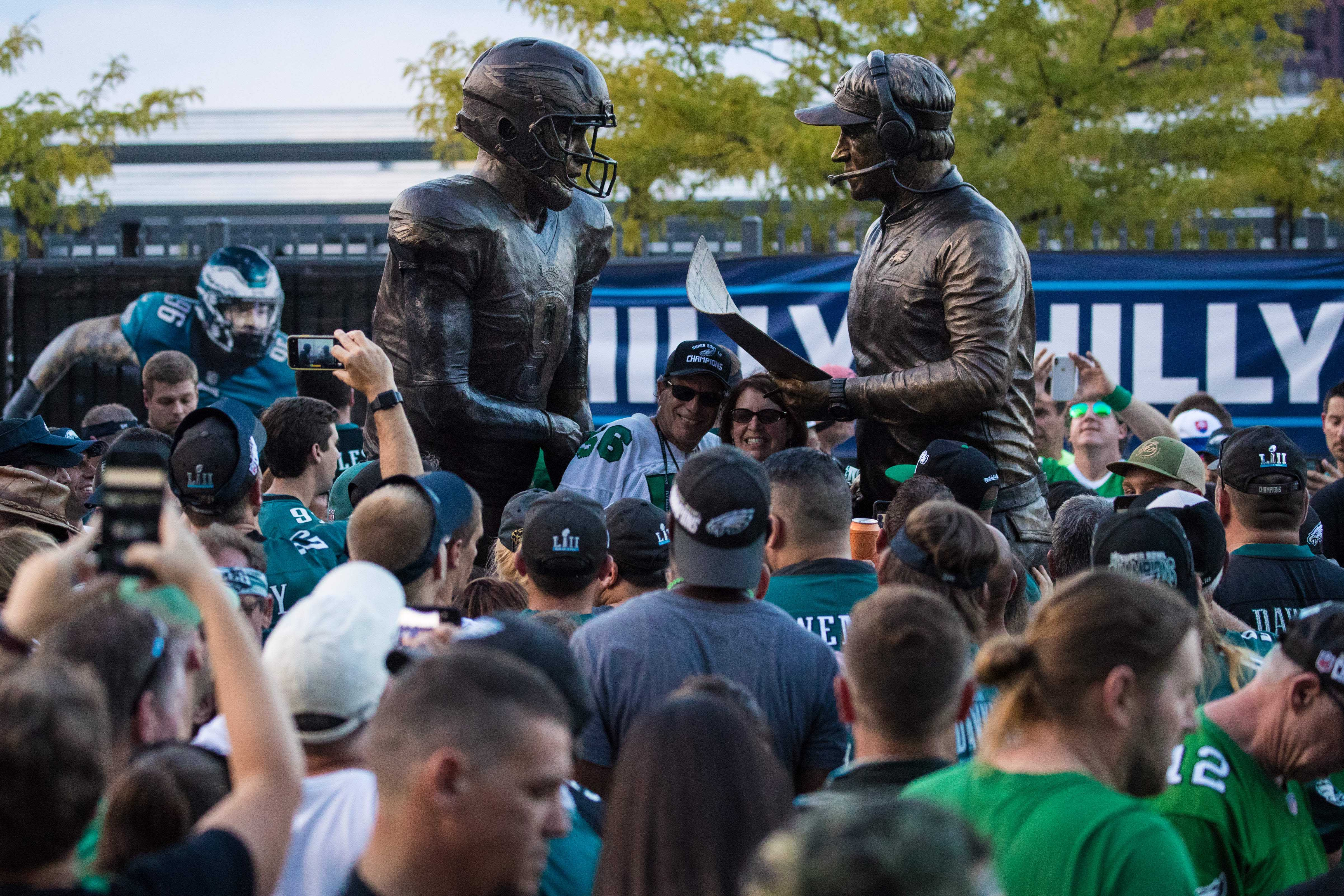 Philadelphia Eagles fans crowd around a new statue depicting head coach Doug Pederson (right) and quarterback Nick Roles (left) during Super Bowl LII. - Packers QB Carted Off In Clash With Bears