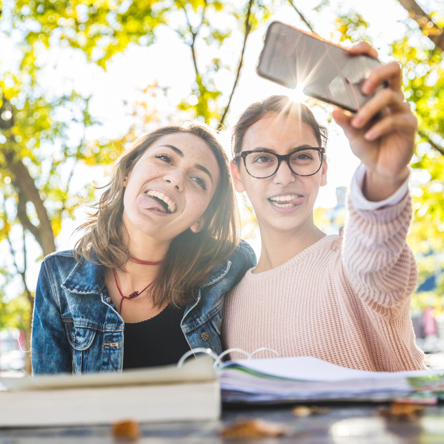 Girls studying together at park and taking a funny selfie. Happy best friends with books having fun while studying. Friendship and lifestyle concepts.