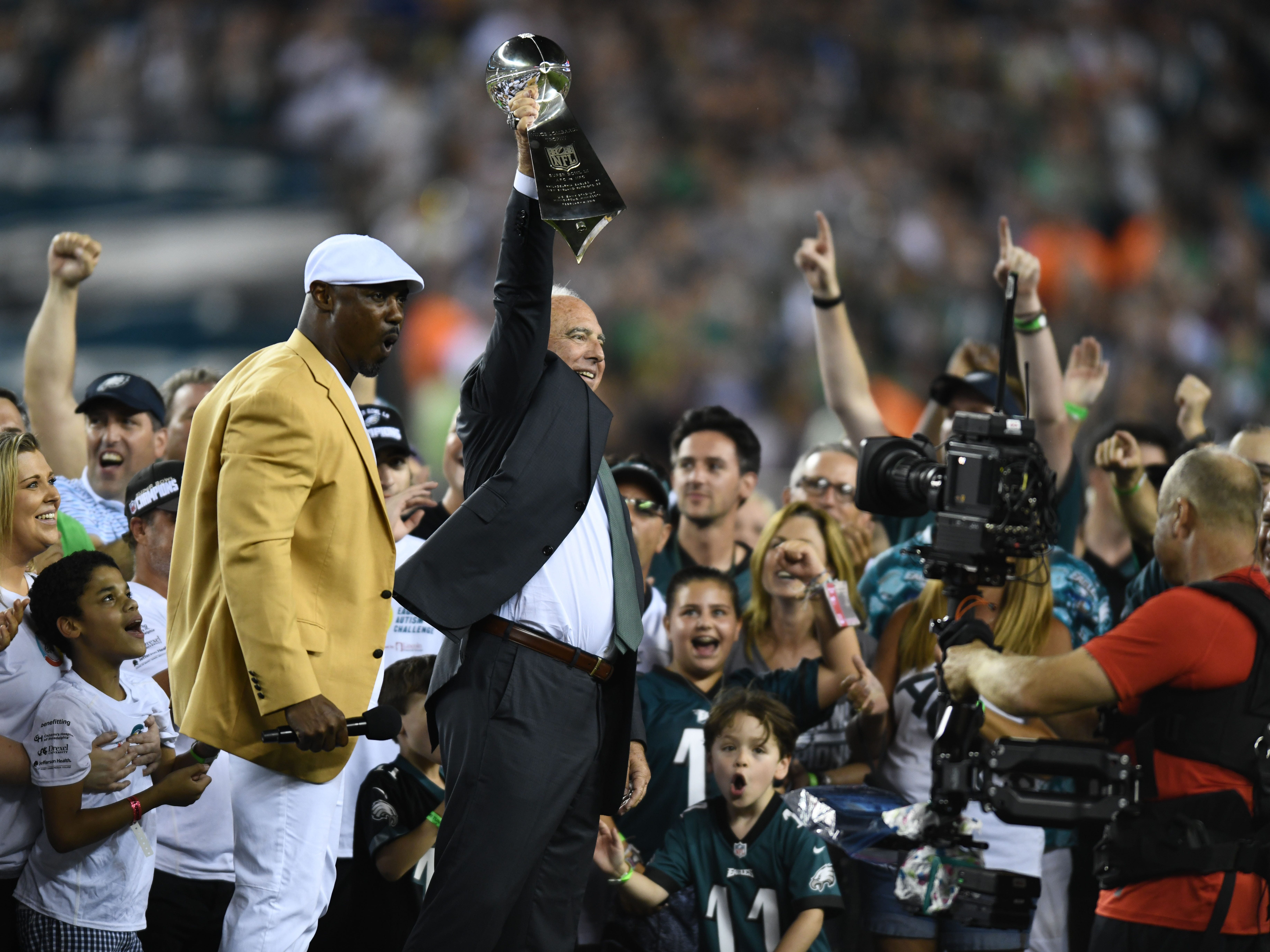 Philadelphia Eagles owner Jeffrey Lurie holds up the Lombardi Trophy as Hall of Fame safety Brian Dawkins reacts during the pregame celebration of the Super Bowl LII championship at Lincoln Financial Field.