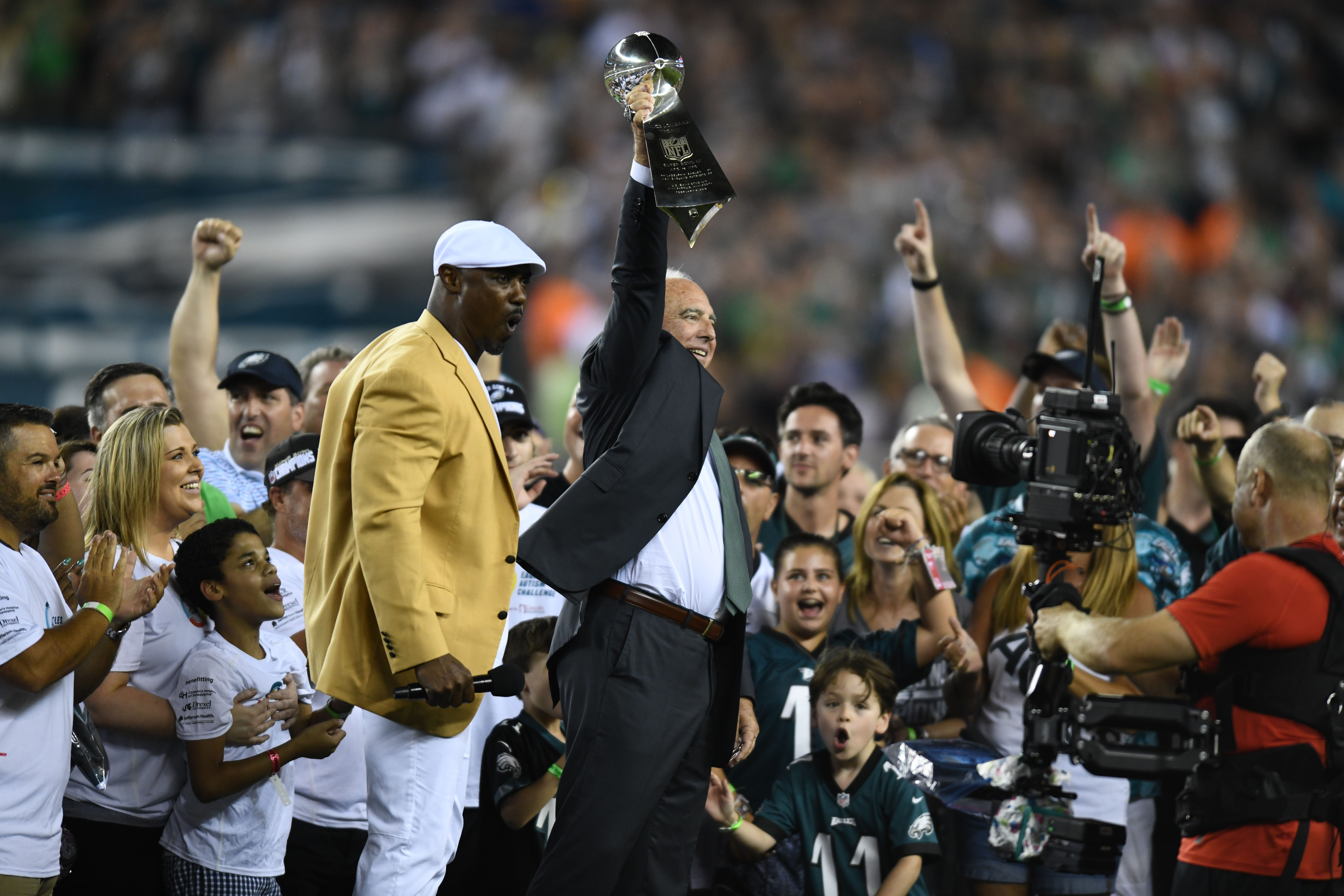 Philadelphia Eagles owner Jeffrey Lurie holds up the Lombardi Trophy as Hall of Fame safety Brian Dawkins reacts during the pregame celebration of the Super Bowl LII championship at Lincoln Financial Field. - Packers QB Carted Off In Clash With Bears