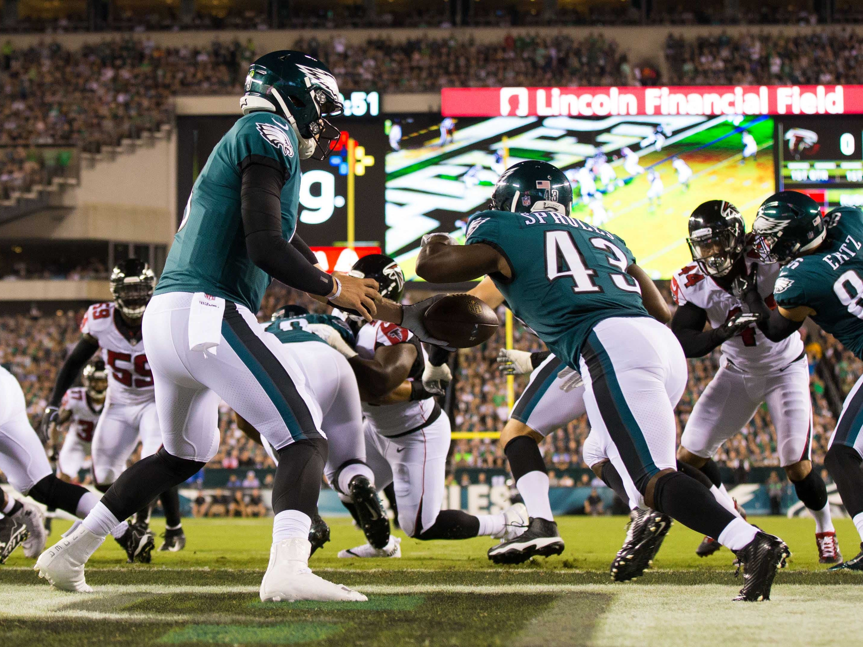 Philadelphia Eagles quarterback Nick Foles hands off to running back Darren Sproles during the first quarter against the Atlanta Falcons at Lincoln Financial Field.