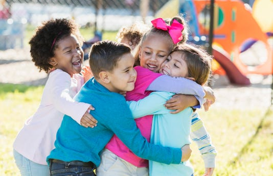 Children Playing Outdoors On Playground Hugging