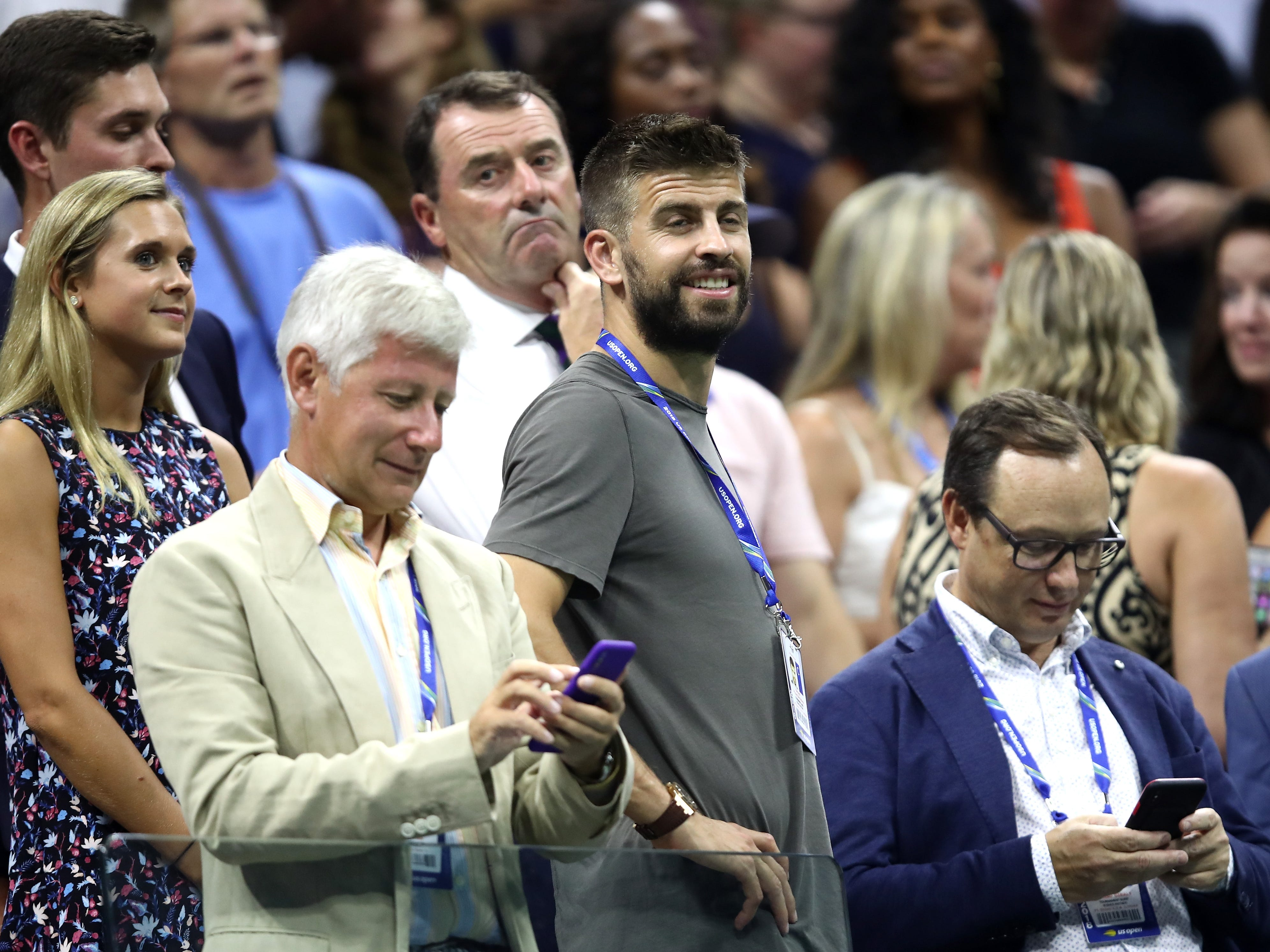 FC Barcelona soccer player Gerard Pique, front center, watches the semifinal match between Naomi Osaka and Madison Keys.