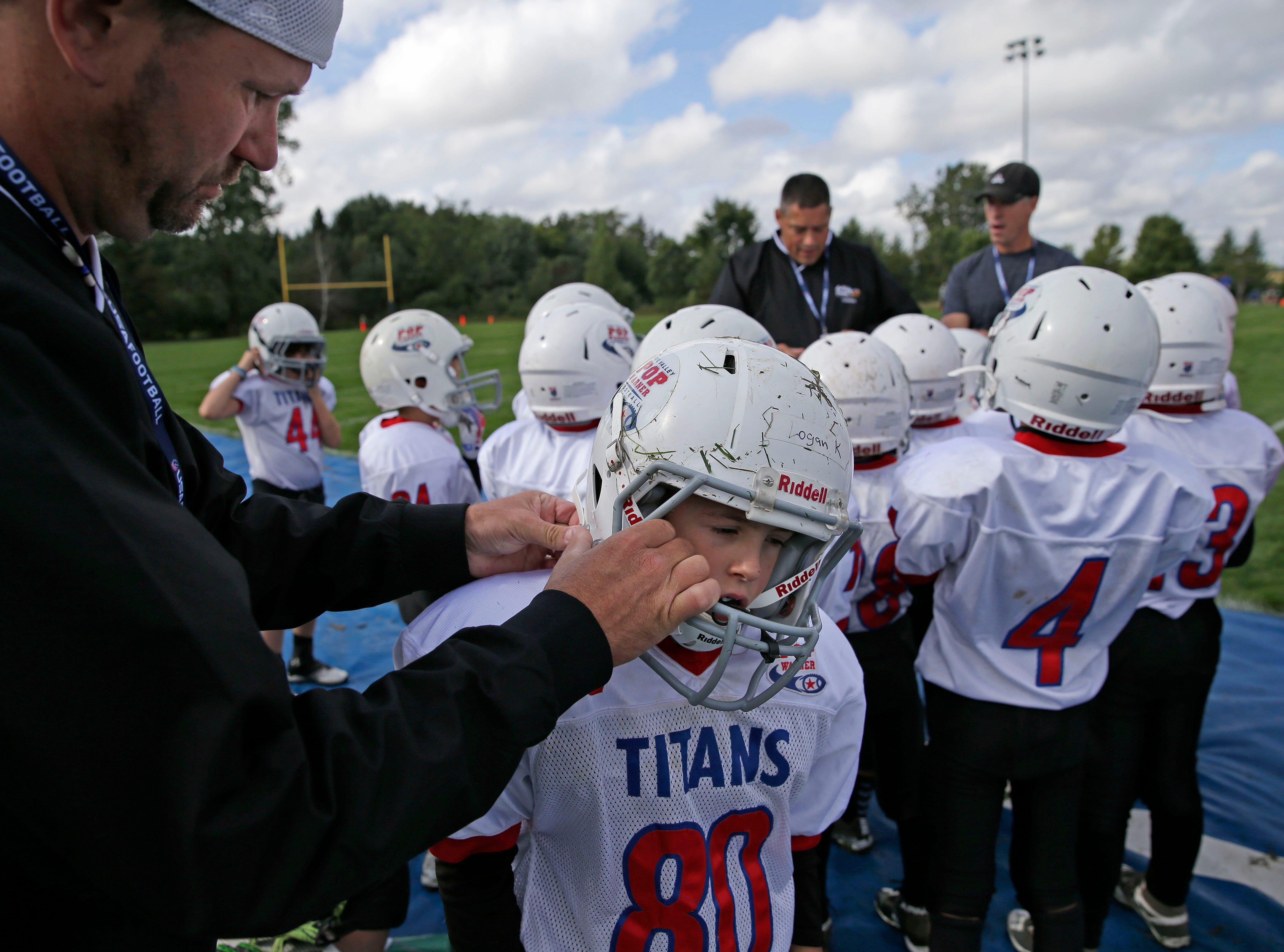 Logan Kittoe of the Titans gets help with his helmet as Fox Valley Pop Warner Football opens the season Saturday, September 8, 2018, at Plamann Park in Grand Chute, Wis.