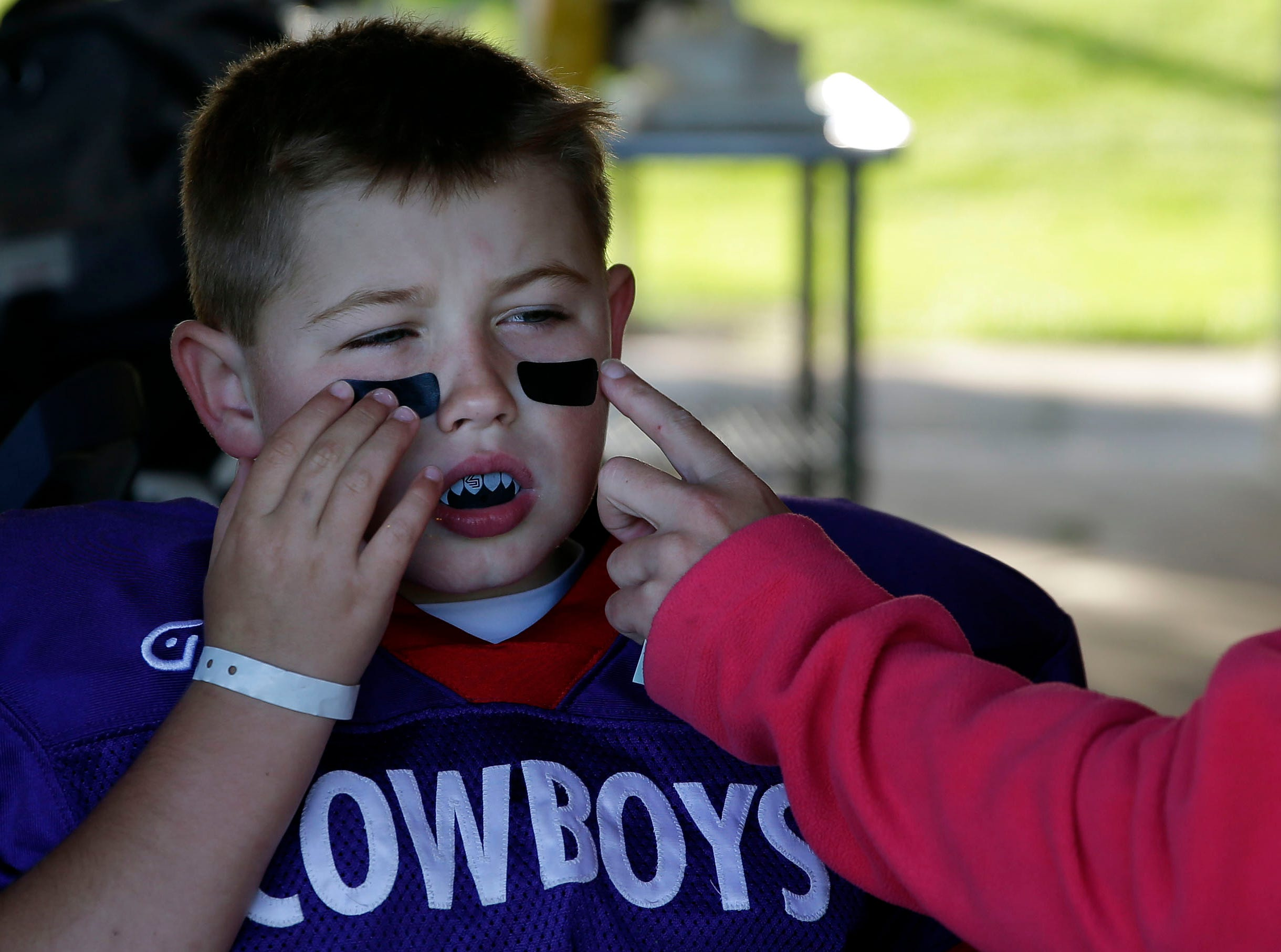 Jaxon Hill of the Cowboys gets help with eye black from his mother, Heather, as Fox Valley Pop Warner Football opens the season Saturday, September 8, 2018, at Plamann Park in Grand Chute, Wis.