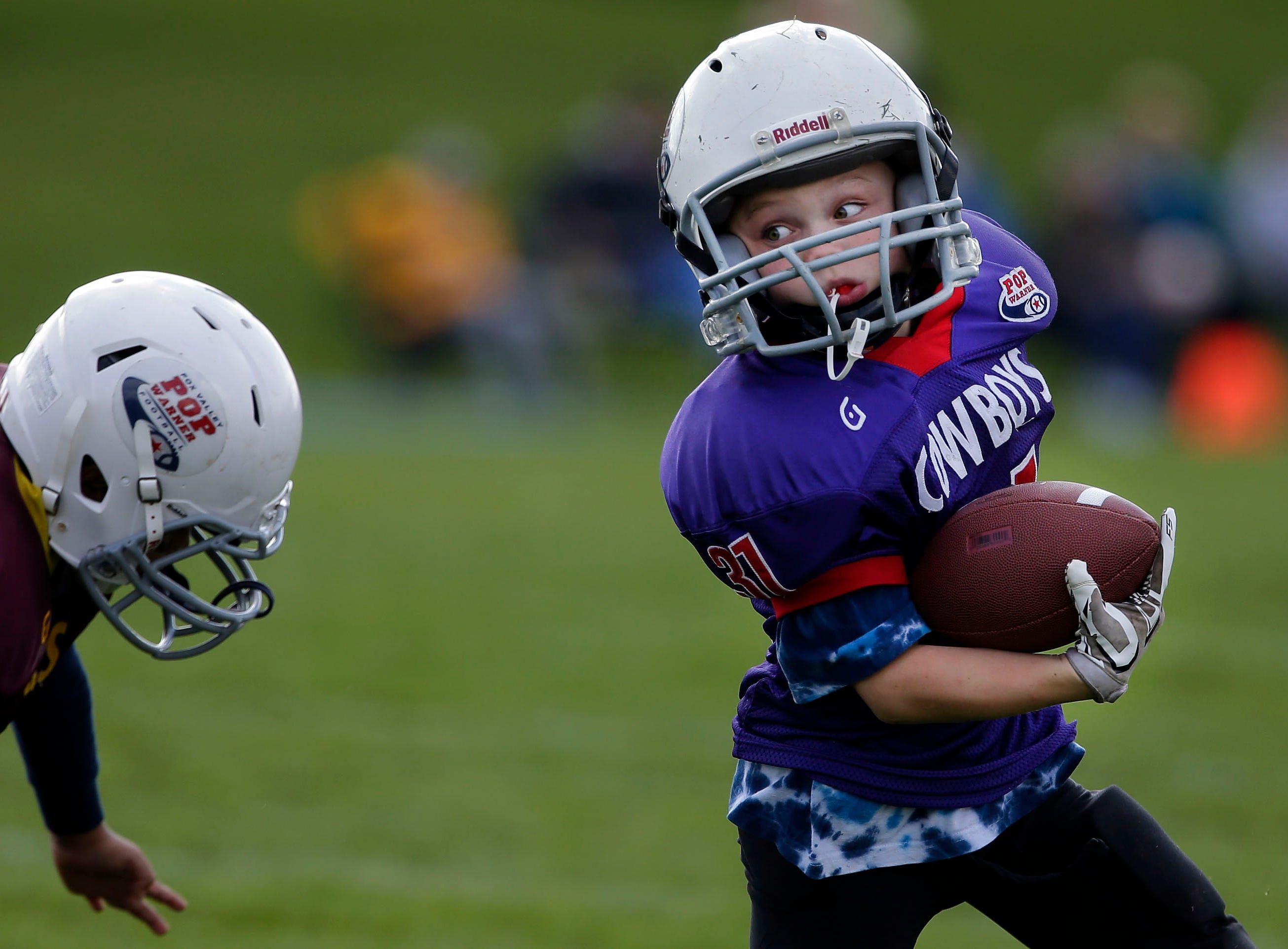 Anthony Reischl of the Cowboys gets away from Richard Ayon of the Foxes as Fox Valley Pop Warner Football opens the season Saturday, September 8, 2018, at Plamann Park in Grand Chute, Wis.