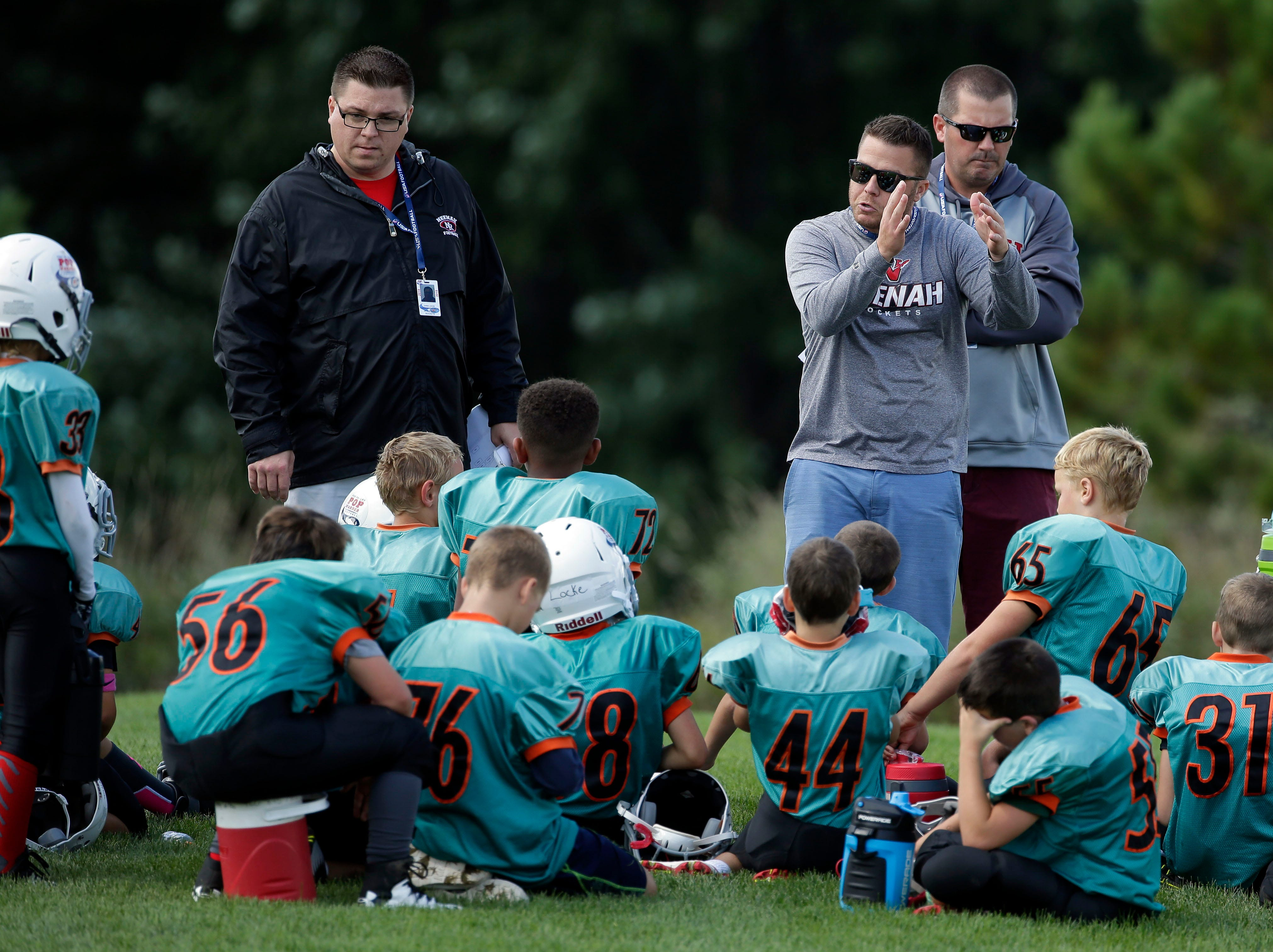 Coaches get a few minutes during the half to talk with their team as Fox Valley Pop Warner Football opens the season Saturday, September 8, 2018, at Plamann Park in Grand Chute, Wis.