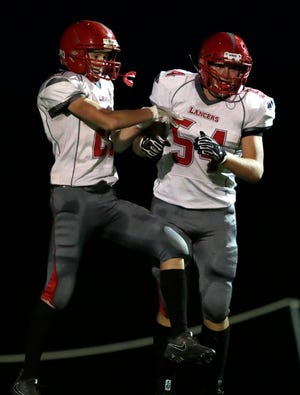 Manitowoc Lutheran's Evan Lischka, left, and Korey Garceau celebrate after Lischka scored a touchdown against Menasha St. Mary on Friday in Fox Crossing.