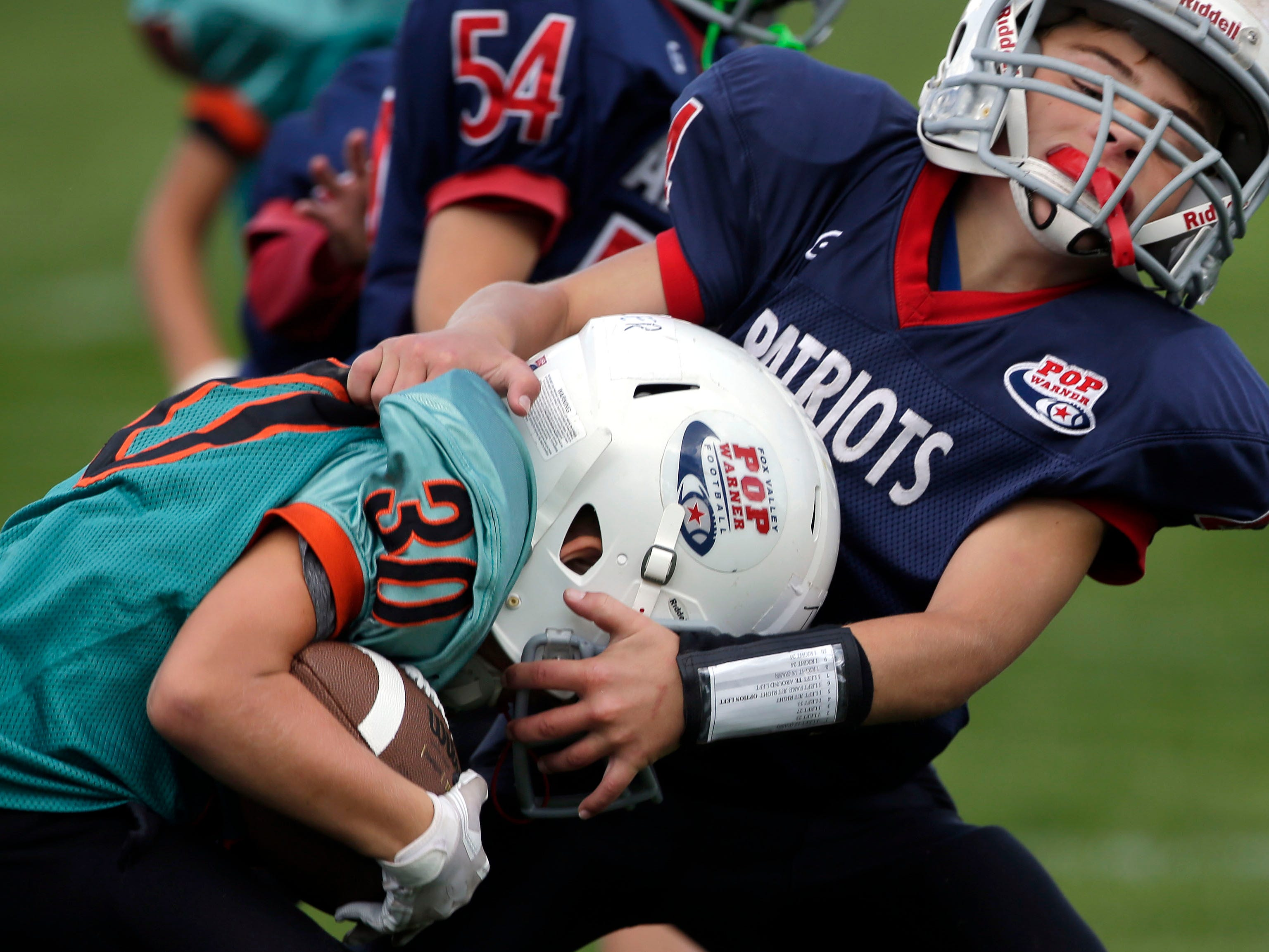 Tyler Clark of the Rockets is tackled by AJ Pheifer of the Patriots as Fox Valley Pop Warner Football opens the season Saturday, September 8, 2018, at Plamann Park in Grand Chute, Wis.