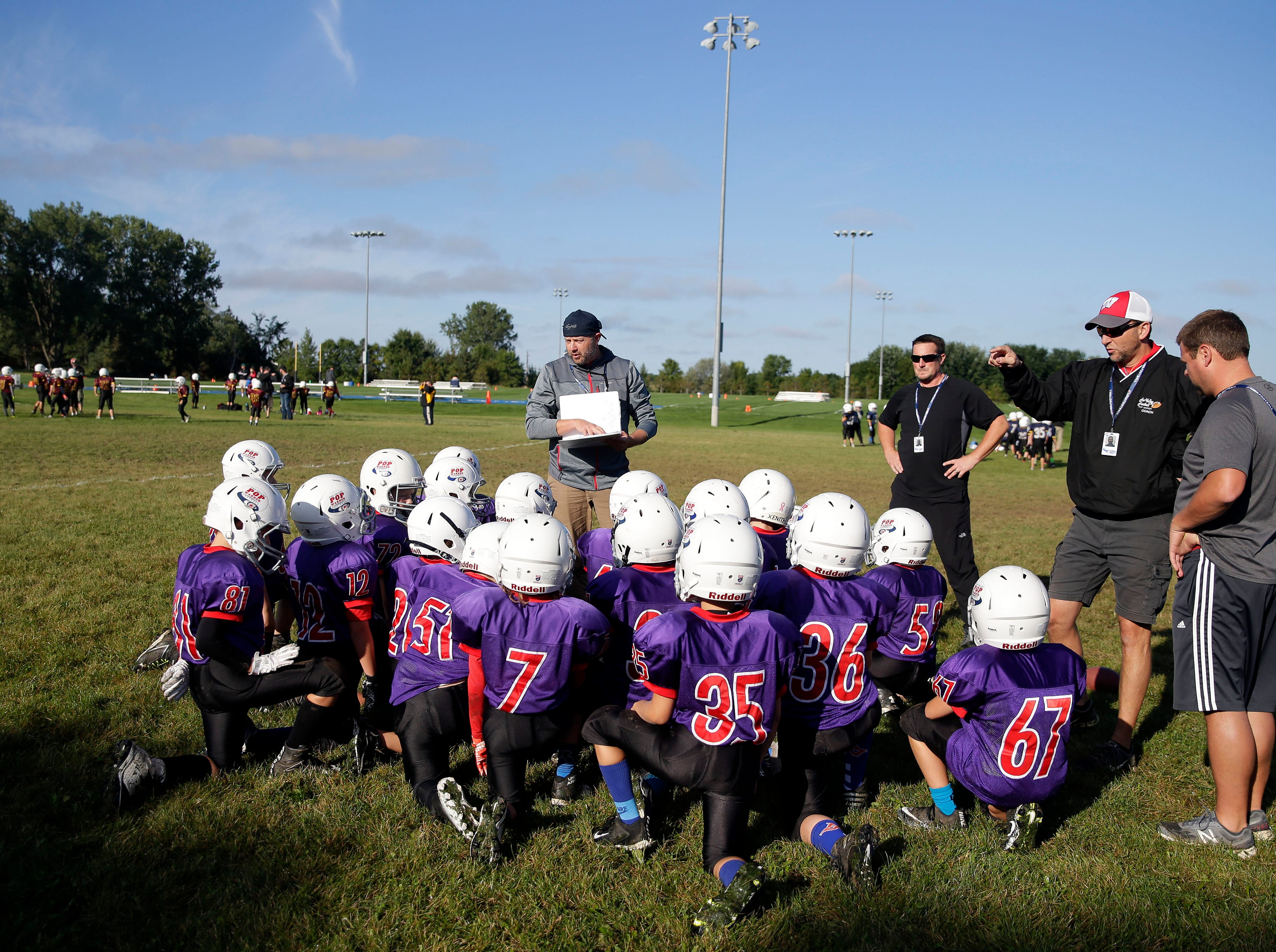 Coach Adam Landsverk, center, and assistants David Gaskill, Clay Tylinski and John Toonen get the Cowboys ready for their game as Fox Valley Pop Warner Football opens the season Saturday, September 8, 2018, at Plamann Park in Grand Chute, Wis.Ron Page/USA TODAY NETWORK-Wisconsin