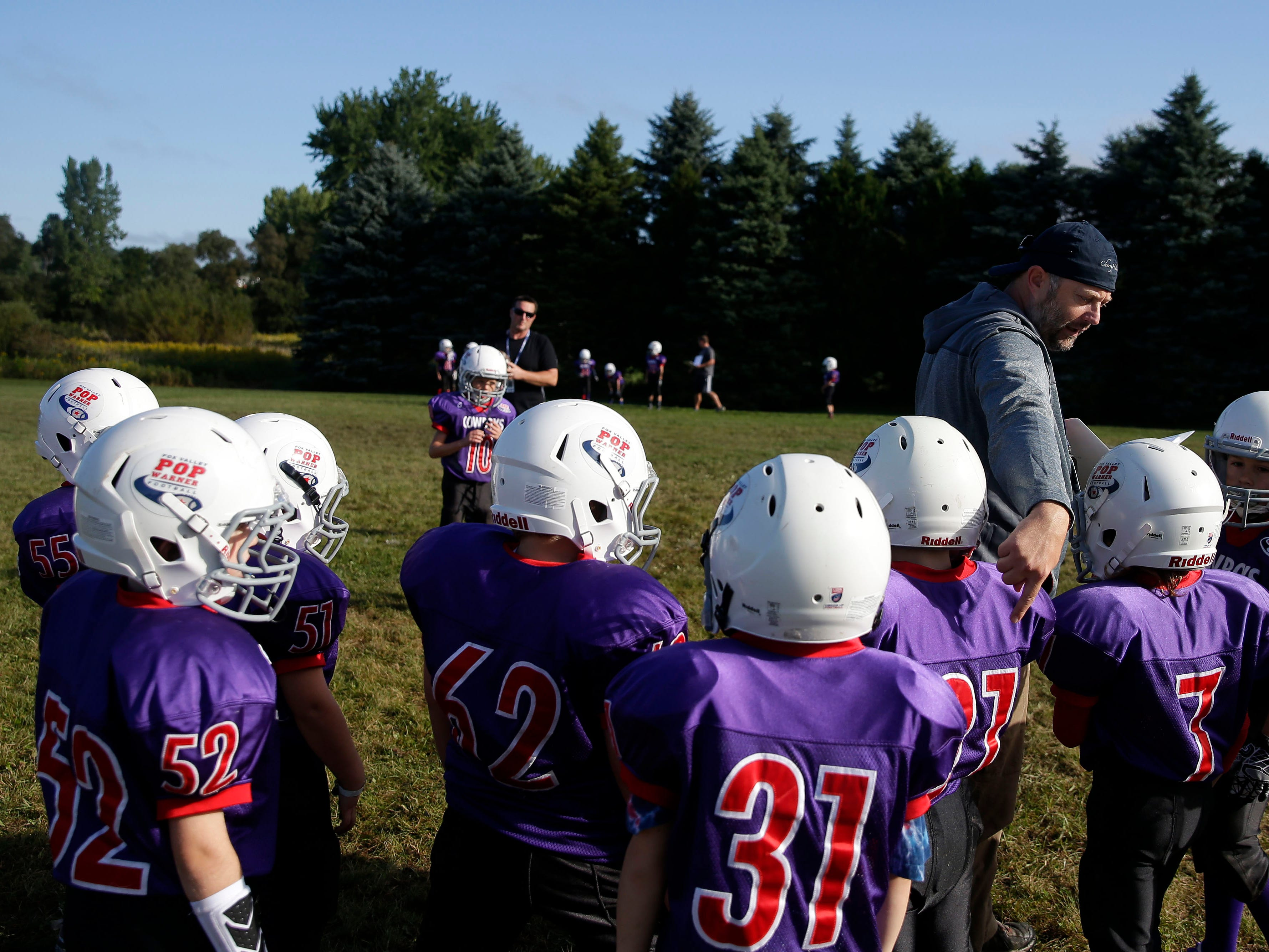 Coach Adam Landsverk of the Cowboys instructs players where to go in a huddle as Fox Valley Pop Warner Football opens the season Saturday, September 8, 2018, at Plamann Park in Grand Chute, Wis.