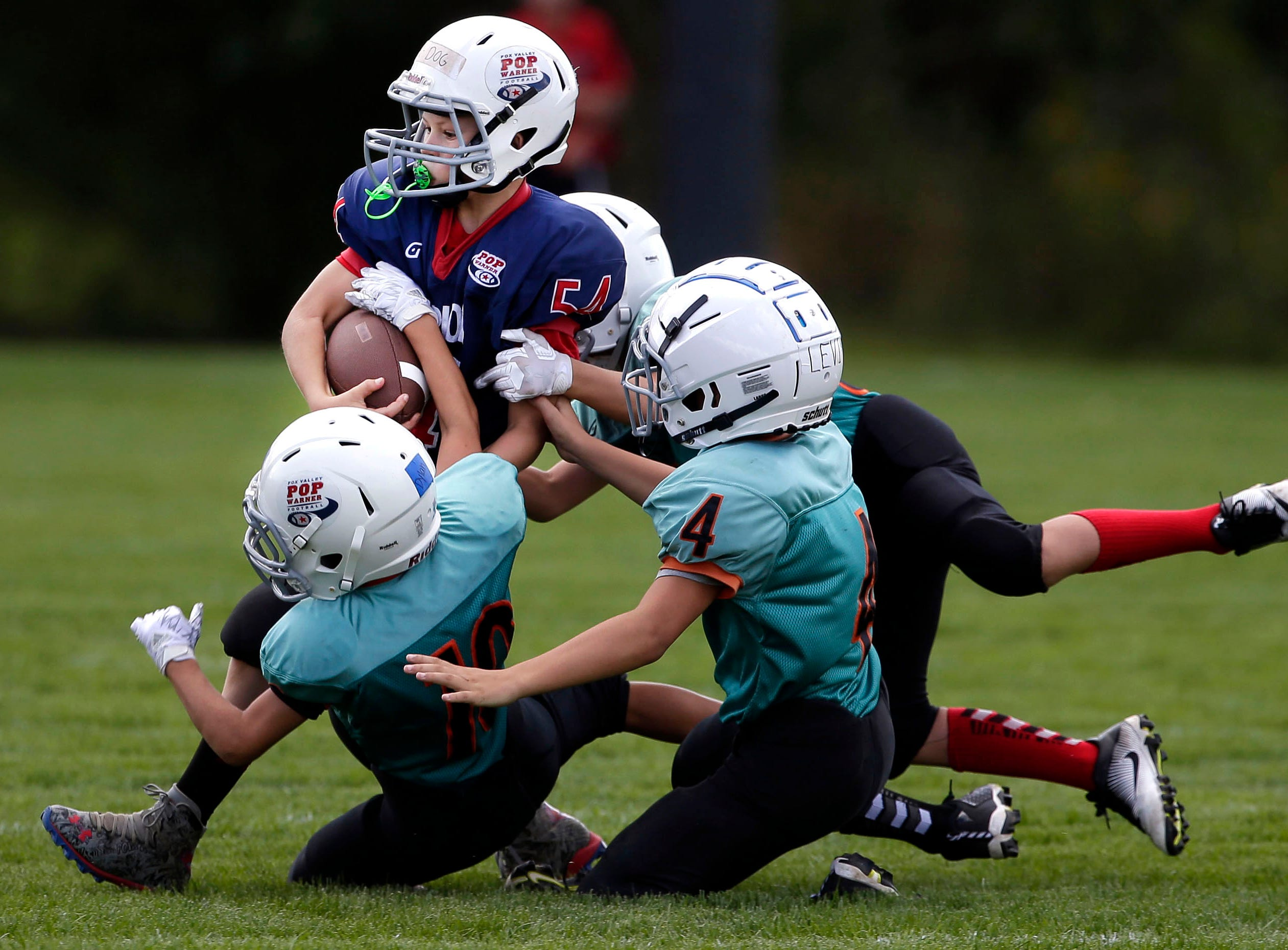 Kolten Jens of the Patriots is surrounded by the Rockets defense as Fox Valley Pop Warner Football opens the season Saturday, September 8, 2018, at Plamann Park in Grand Chute, Wis.