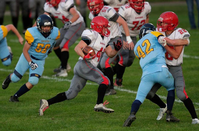 Manitowoc Lutheran's Ryan Wendt (41) runs for a gain against Menasha St. Mary on Friday in Fox Crossing.