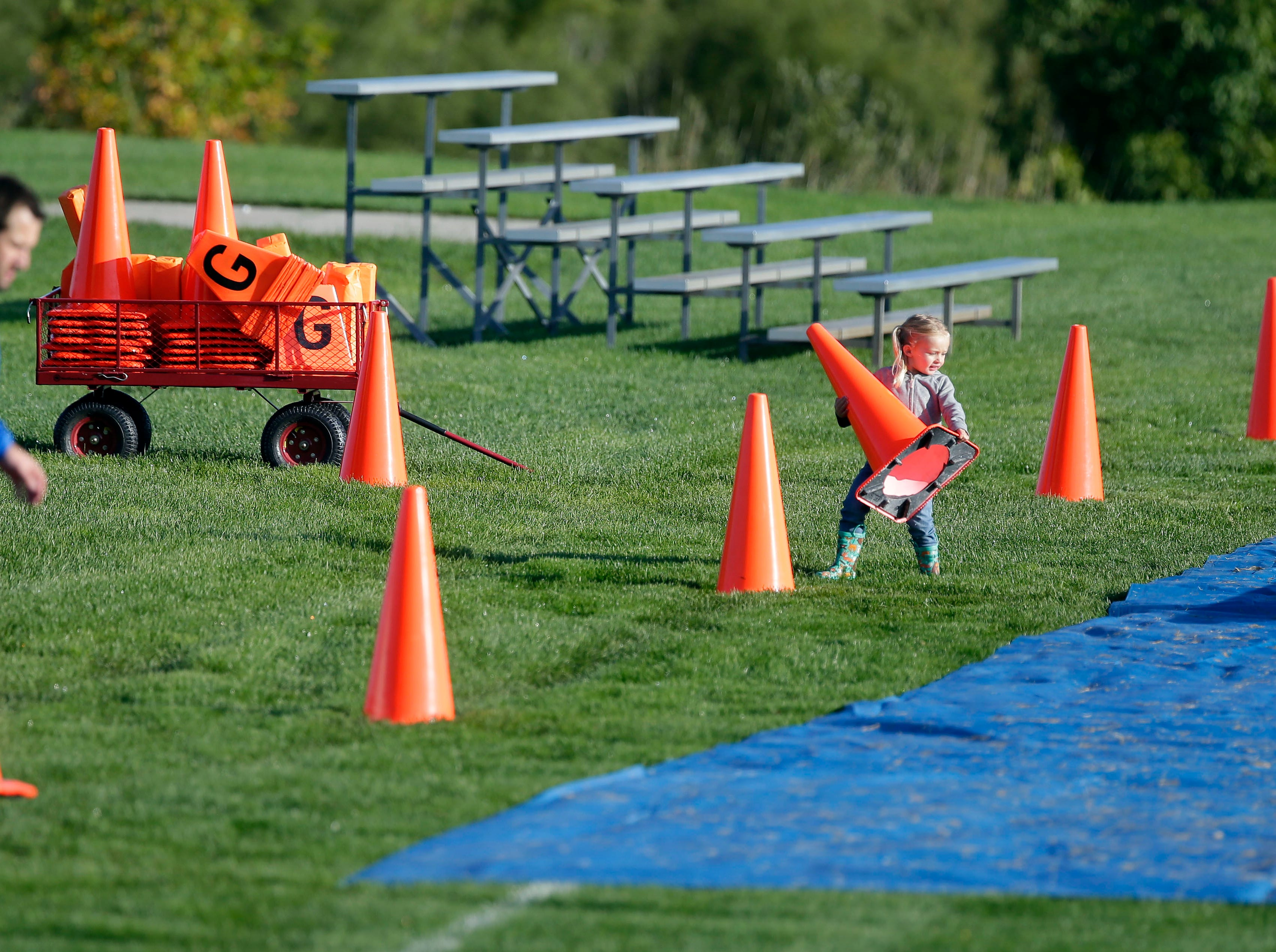 Sienna Springer helps her father, Will, a board member of Fox Valley Pop Warner Football, get cones in place before the first game of the season gets underway Saturday, September 8, 2018, at Plamann Park in Grand Chute, Wis.