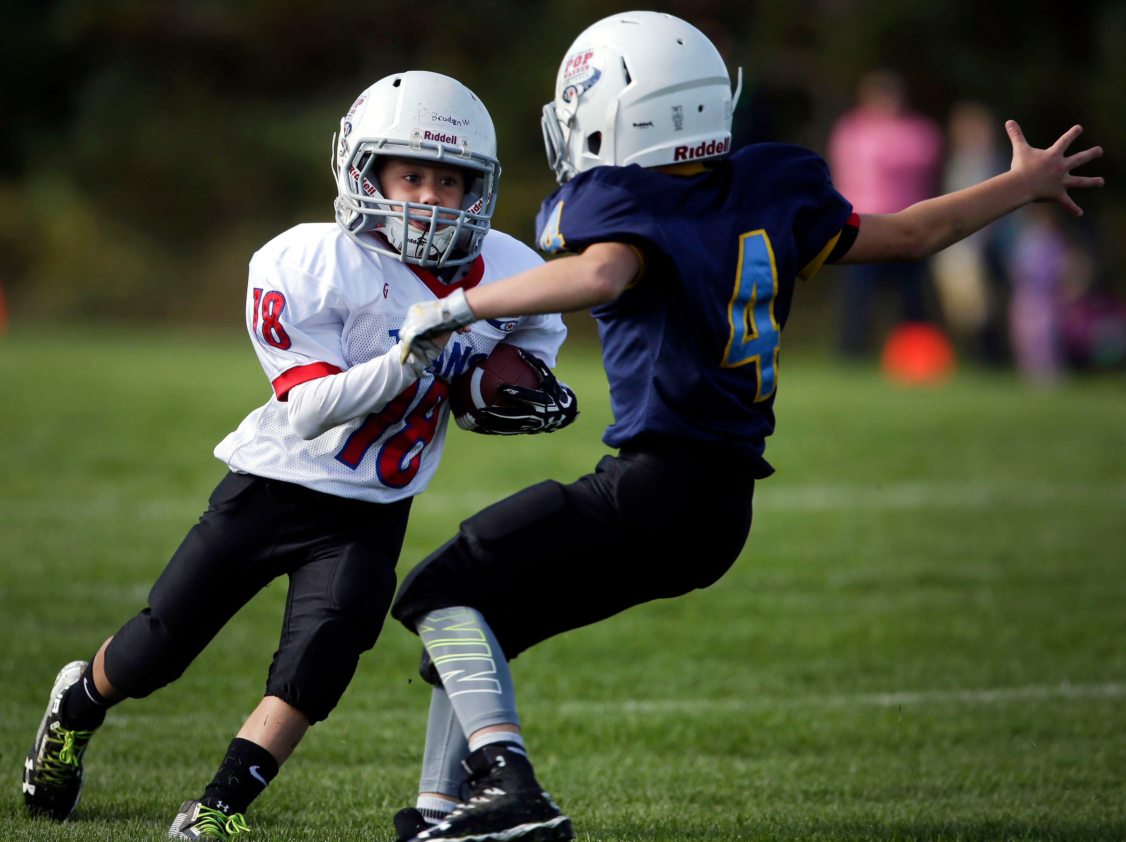 Braden Wills of the Titans cuts against defender Greyson Peters of the Pioneers as Fox Valley Pop Warner Football opens the season Saturday, September 8, 2018, at Plamann Park in Grand Chute, Wis.Ron Page/USA TODAY NETWORK-Wisconsin