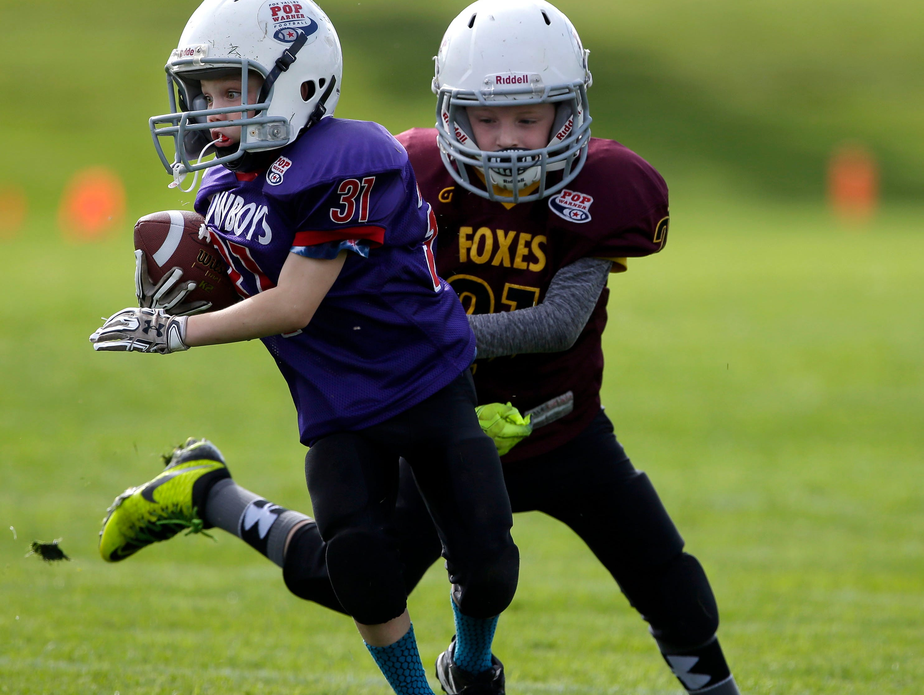 Anthony Reischl of the Cowboys works to get away from Evan Schmidt of the Foxes as Fox Valley Pop Warner Football opens the season Saturday, September 8, 2018, at Plamann Park in Grand Chute, Wis.Ron Page/USA TODAY NETWORK-Wisconsin