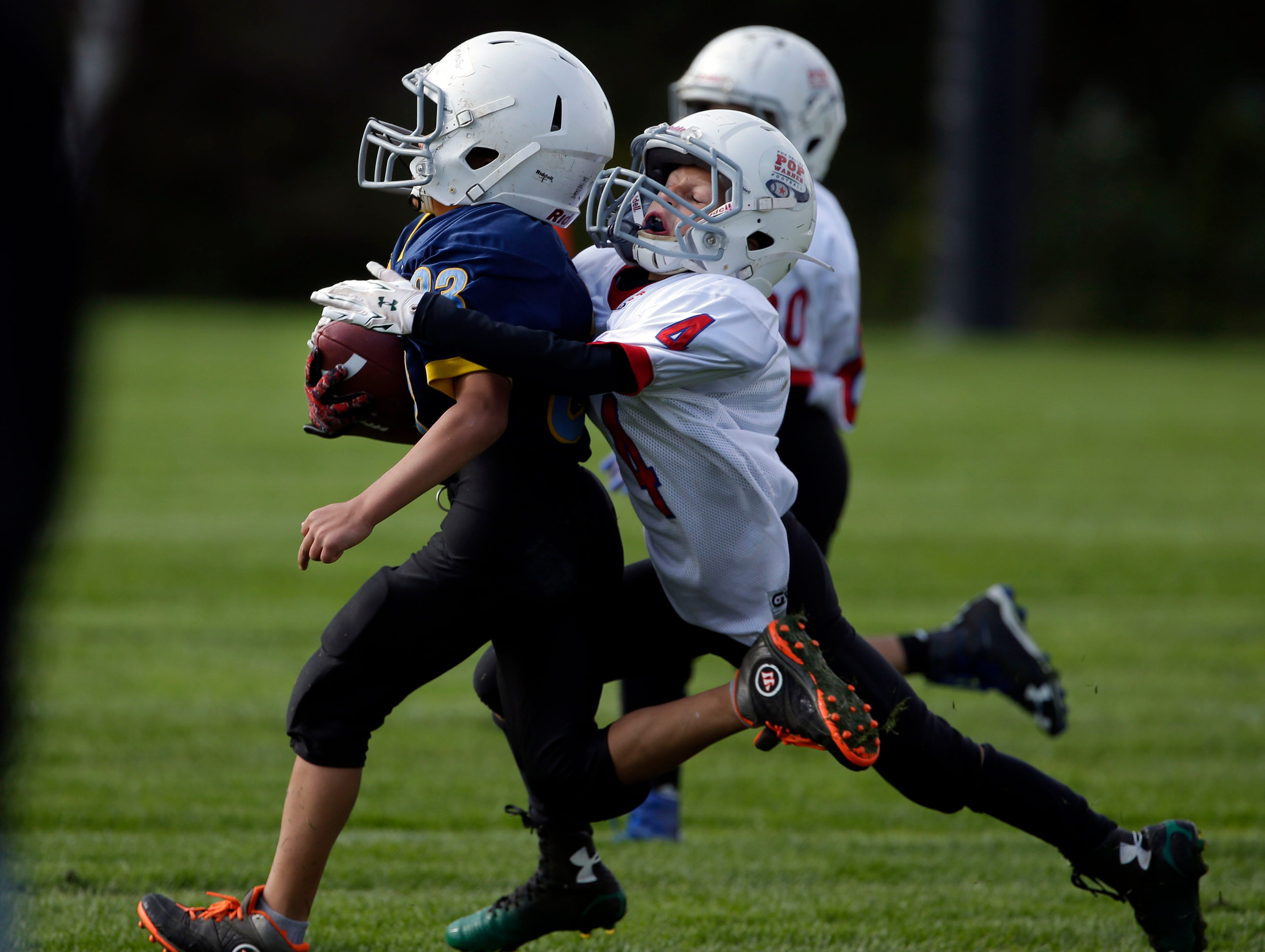 Samuel Gloudemans of the Pioneers is tackled by Rylan Jochimsen of the Titans as Fox Valley Pop Warner Football opens the season Saturday, September 8, 2018, at Plamann Park in Grand Chute, Wis.Ron Page/USA TODAY NETWORK-Wisconsin