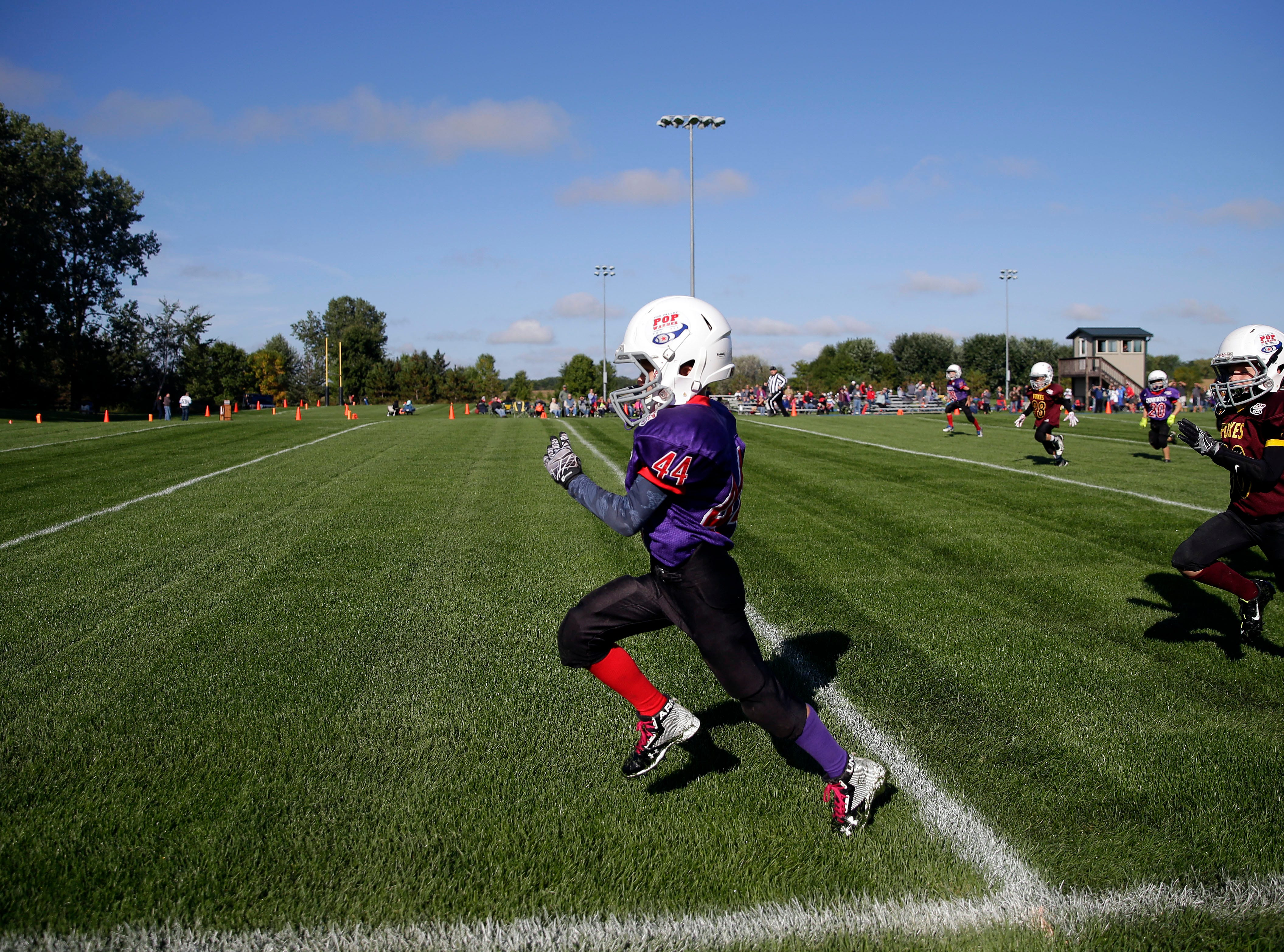 Carson Tylinski of the Cowboys runs for a touchdown that is called back as Fox Valley Pop Warner Football opens the season Saturday, September 8, 2018, at Plamann Park in Grand Chute, Wis.