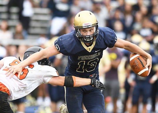Freehold Borough QB Matt Krauss drives past Middletown North's Steven Holler as Freehold Borough defeats Middletown North 22-20 on 9/8/2018