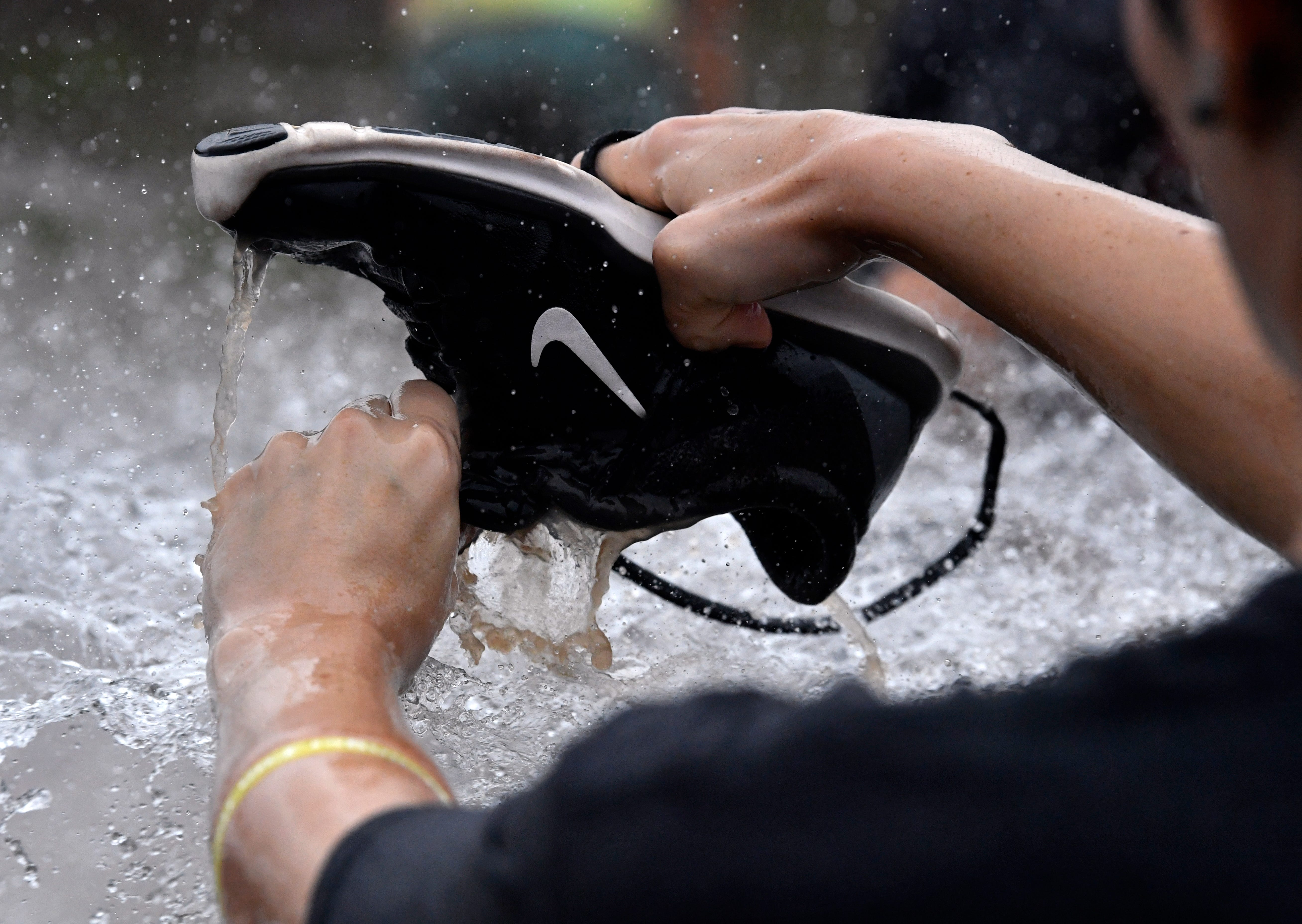 A runner washes her shoe out at the end of a course, courtesy of a tanker truck. The eighth annual Mudslinger Fun Run was held Saturday at Seabee Park. The nearly three-mile course featured numerous obstacles, both man- and mud-made. It benefits Abilene Youth Sports Authority.
