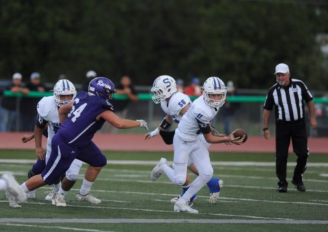 Stamford quarterback Peyton Bevel (11) eludes the pass rush from Roscoe's Garrett Bowers on Sept. 7, 2018.
