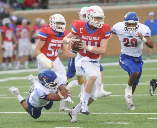 Cooper's Tavian Bonds, left, can't get to Grapevine quarterback Cade Rhodes before Rhodes throws the ball away. Grapevine won the game 31-13 on Friday, Sept. 7, 2018 at Apogee Stadium in Denton.